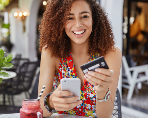 Internet banking and ecommerce concept. Happy young smiling female with Afro hairstyle, uses modern cell phone and credit card for online shopping, enjoys fresh fruit smoothie in terrace bar.