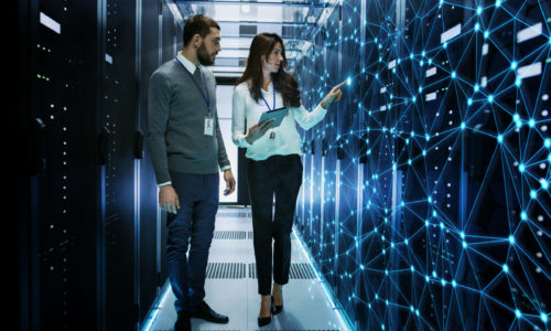 Female and Male IT Engineers Discussing Technical Details in a Working Data Center/ Server Room with Internet Connection Visualization.